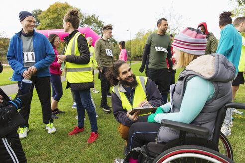 Woman in wheelchair checking in with volunteer at charity race in park - CAIF20341