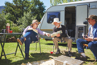 Active senior friends reading outside camper van at sunny summer campsite - CAIF20383