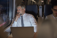 Serious, thoughtful businessman working at laptop, looking out window on passenger train at night - CAIF20407