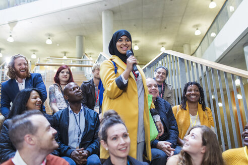 Smiling woman in hijab speaking with microphone in conference audience - CAIF20413