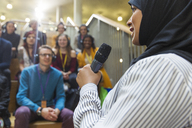 Smiling businesswoman in hijab speaking to audience with microphone - CAIF20416