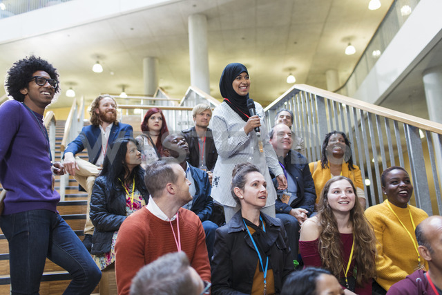 Smiling woman in hijab talking with microphone in conference audience - CAIF20431