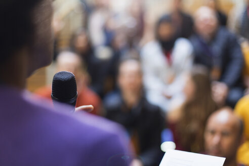 Businessman with microphone speaking to conference audience - CAIF20446