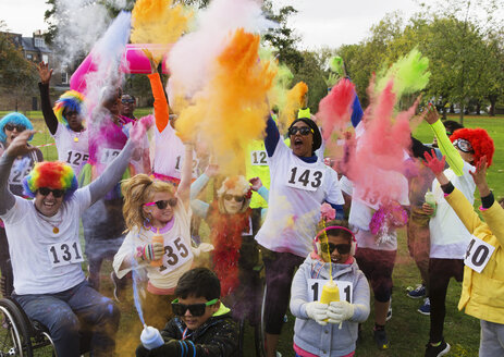 Playful charity run runners celebrating with holi powder in park - CAIF20461