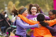 Enthusiastic female runners finishing charity run, celebrating - CAIF20464