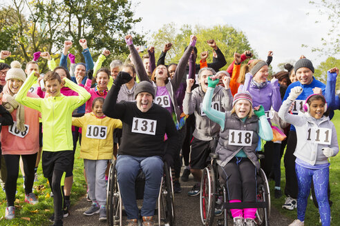 Portrait enthusiastic crowd cheering at charity run in park - CAIF20476