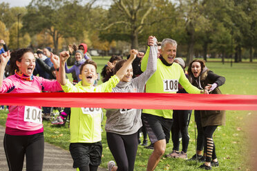 Enthusiastic family running, nearing charity run finish line - CAIF20479