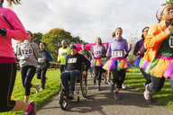 Man in wheelchair among runners at charity race in park - CAIF20497