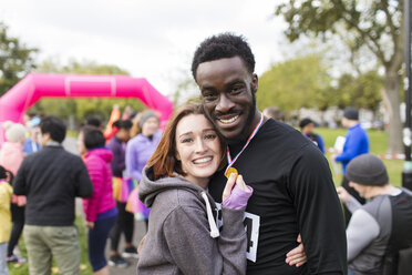 Portrait happy couple runners with medal at charity run in park - CAIF20500