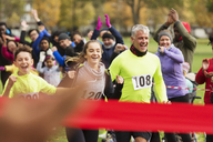 Enthusiastic family running, nearing finish line at charity run in park - CAIF20503