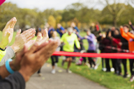 Spectators clapping for runners nearing finish line at charity event - CAIF20506