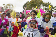 Portrait playful runners with holi powder at charity run in park - CAIF20515