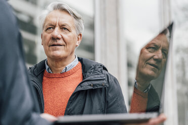 Senior man looking at man holding laptop outdoors - GUSF00646