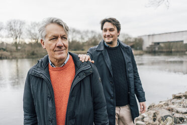 Confident senior man and young man standing at the riverside - GUSF00655