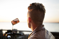 Rear view of motorcyclist looking at sea view during sunset - CAVF48204