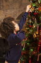 Side view of boy decorating Christmas tree at home - CAVF48276