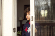 Thoughtful boy looking through window at home - CAVF48279