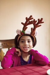 Portrait of happy girl wearing reindeer headband while sitting at table - CAVF48288