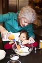 Senior woman with granddaughter preparing food at home - CAVF48600