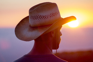 Rear view of man wearing hat looking away during sunset - CAVF48708