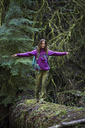 Woman with arms outstretched walking on fallen tree trunk in forest - CAVF48753