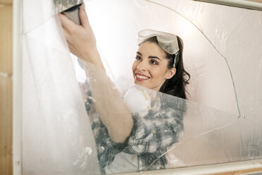 Young woman renovating her new flat, using cartridge dispenser - PESF01034