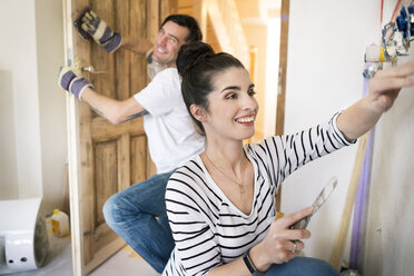 Happy couple renovating new home - PESF01055