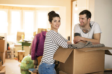 Happy couple moving house, standing by cardboard box - PESF01058