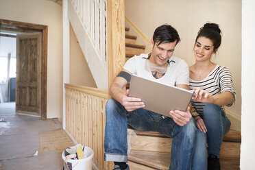 Young couple refurbishing new home, sitting on stairs using digital tablet - PESF01061