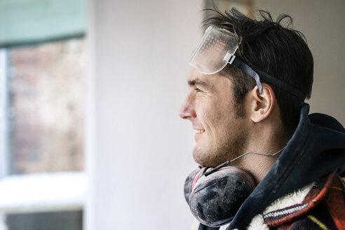 Portrait of a handyman , renovating flat, looking through window - PESF01067
