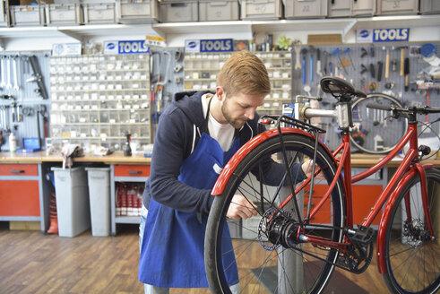 Bicycle mechanic working in his repair shop - LYF00812