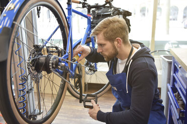 Bicycle mechanic in his repair shop, portrait - LYF00821