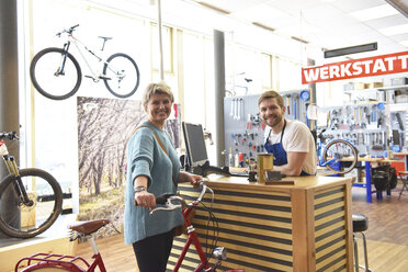 Salesperson helping customer in bicycle shop - LYF00824