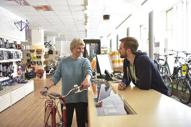 Salesperson helping customer in bicycle shop - LYF00833