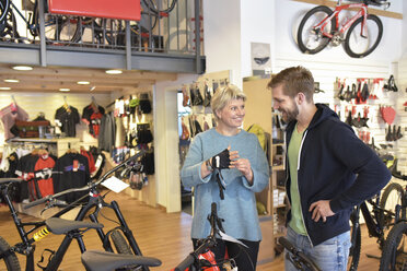 Salesperson helping customer in bicycle shop - LYF00836