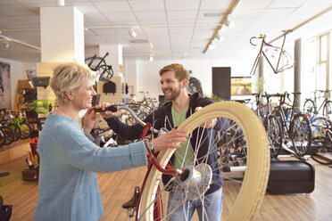 Salesperson helping customer in bicycle shop - LYF00839