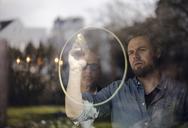 Mature man drawing a circle on window pane, senior man watching - GUSF00665
