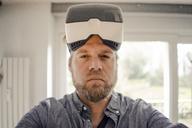 Mature man taking selfie of himself, wearing VR glasses, looking cool - GUSF00668