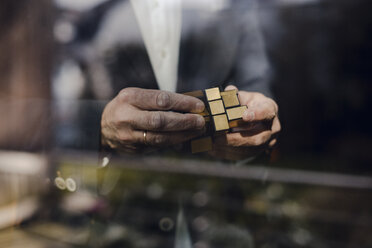 Senior businessman putting together puzzle cube - GUSF00686