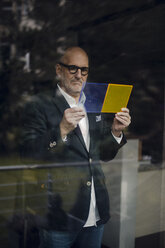 Senior architect standing at window, choosing materials - GUSF00689