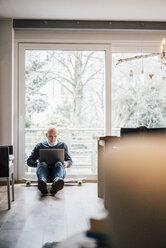 Senior man sitting on ground, using laptop - GUSF00701