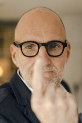 Senior man with glasses, focussing on his index finger - GUSF00713