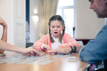 Family playing memory on table at home - MOEF01077