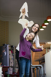 Happy mother and daughter throwing paper plane together at home - MOEF01095