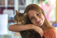 Portrait of smiling girl with her tabby cat - SARF03677