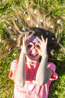 Smiling girl lying on grass in spring with daisies on hair forming spectacles with fingers - SARF03680