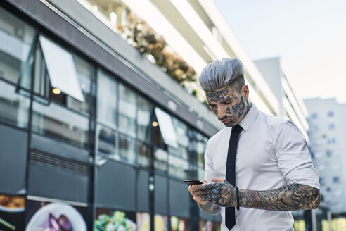 Young businessman with tattooed face using smartphone - ZEDF01331