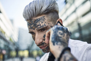 Young businessman with tattooed face, talking on he phone - ZEDF01334