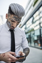 Young businessman with tattooed face using smartphone - ZEDF01337