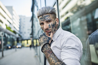 Young businessman with tattooed face walking in the city, portrait - ZEDF01340